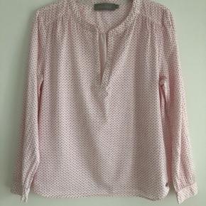 Den er hvid med er lille pink mønster. Lille i str. passer M/L