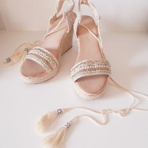 Lyse sandfarvede wedge sandaler fra Buch med perler og pailletpynt foran. Med bindebånd. Aldrig brugt.