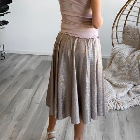 Fortryllende nederdel i fantastisk glittermateriale. Perfekt til en særlig anledning, hvor man ønsker lidt ekstra glimmer eller til hverdag med sneakers. (Det glitrende er både glimmer og tråde der er skinnende og giver denne fantastiske effekt) Den er ny og stadig med pris mærke.   Kjolen er i 2 lag stof, så den giver et flot fald.  Almindelig i størrelsen. Modellen har S på og bruger S normalt. 100% Polyester  Sendes med DAO til 40,- med mindre andet ønskes. Fra røgfrit og dyrefri hjem.