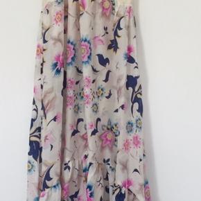 Smuk boheme agtig silkekjole med fantastisk smukke blomster. Masser af vidde.  Overdelen er lavet af bomuld med broderi foran og perlemors knapper.  Den er lidt kortere foran end bagtil.  Virkelig smuk sommerkjole som kun sælges fordi jeg ikke kan passe den mere - og nok heller ikke kommer til det. Brugt få gange.   Fra røgfrit og dyrefrit hjem   Sender gerne flere billeder på mail