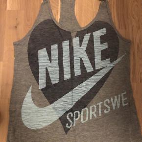 Nike sporttop med logo, i størrelse Small.   Brugt nogle gange, men fejler ikke noget.  Loose fit.   Kom gerne med et bud! :D  Tjek gerne mine andre annoncer :D