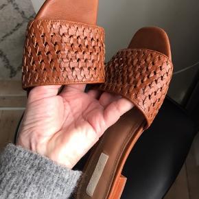 Læder slippers i cognac farvet flettet læder. Har desværre fået et par hakker i hælene, og prisen er sat efter det.  Gav selv 399. Sælger dem kun fordi jeg også har samme model i sort.  Køber betaler Porto.