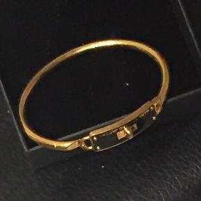 Smukt smukt armring fra Marc by Marc Jacobs i guld og sort, ka åbnes.  Str. Ca. 17 cm.  Prisen er fast.