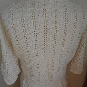Cremefarvet strikket bolero/kort cardigan. 3/4 lange ærmer med en skøn detalje se billedet og fine knapper. Det er en lidt kraftig strik så den er god en kølig aften. Porto skal tillægges eller hent den på Amager