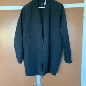 Lang tynd jakke i sort/mørkegrå. Super fed med gode lommer. Skal lige vaskes men fremstår ellers helt som ny.
