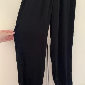 Super dejlige bukser fra MSCH. De er af 100% polyester. De er gået op i sygningen (den yderste) ved skridtet, som ses på sidste billede. Det er ikke noget man lægger mærke til når de er på. Ellers fejler de ingenting og er næsten som nye. De har elastik i taljen. De måler 86 cm fra skridt og ned.  Det er super lækre og afslappende at have på🌸 Flere billeder haves ikke 🤗
