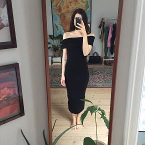 Smuk sort off-shoulder kjole i elastisk rib-strik materiale. Str. XS. Brugt én gang.