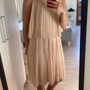 "Super fin beige, plisseret kjole i ""to lag"" fra Selected. Størrelse 36. Lukkes med knap bagpå. Elastik i taljen."
