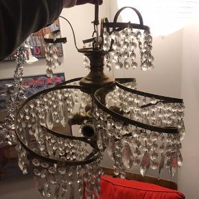 Smuk vintage lysekrone, med fatninger til fem pærer. Lysekronens form laver nærmest en hvirvel, der er svær at fange på billede.