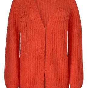 """Lidt svært at beskrive om den er rød eller orange, jeg tror det kommer an på lyset man er i, eller hvad man holder den op i mod. Super god kvalitet, brugt to gange. Den kan let """"trimmes"""" med en skraber eller sådan en strik shaver. Den er lavet af 40% nylon, 30% uld og 30% mohair"""