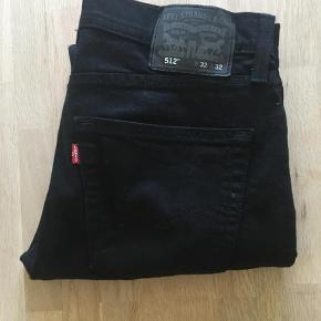 """Varetype: Jeans Størrelse: 32/32"""" Farve: Sort  Helt nye sorte Levis. Købt i USA, desværre for små. Tror at de hedder Slim Taper Fit, men er ikke sikker (mærker haves ej). Model 512. De er slim og stretchy i stoffet."""