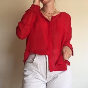 Knaldrød skjorte i et mesh-agtigt stof, med en lomme foran og knapper hele vejen ned.  En af knapperne på højre ærme er før faldet af, men er blevet syet på igen. Skjorten fremtræder, udover dette, som ny.   100% polyester