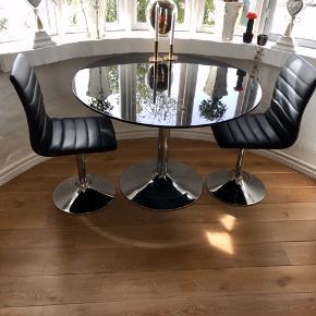Sælger dette fine bord 2 nyer drejestole. Bordet er i sort højglans og er 110 cm i diameter og 77 cm i højden, og har brugsridser. Men kan spraymales hvis det er selv. Eller ved en autolakerer til overkommelig pris.