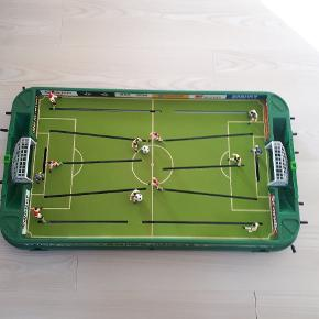 Stiga World Champs fodboldspil. Fungerer perfekt. To fodbolde medfølger.  L: 110 cm B: 50 cm H: 17 cm  Underholdning til ungerne i en coronatid.
