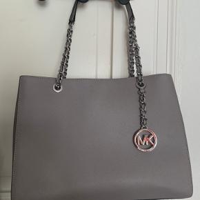 Stor rummelig taske med to store lommer og en lille lomme i midten. Derudover har den 3 små inderlommer.  Længde: 35 cm  Højde: 27 cm Bredde: 15 cm