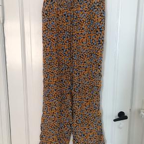 Blomstrede bukser fra nué notes i 100% viskose. Orange og blå blomster på sort baggrund.   Sender ikke men kan afhentes hos mig på Nørrebro 🌸