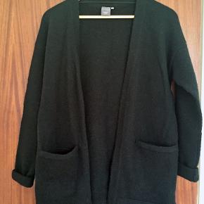 Dejlig lun, mellemlang cardigan. To lommer. Uden lukning. OBS! Kan have tendens til at kradse og samle fnug. 35% uld, 35% akryl, 28% polyamid, 2% elastan. Model: MERCUNA CA