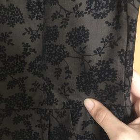 Meget smuk vintage - retro kjole fra 1960'erne. Brun med sorte blomster, stoffet er let skinnende, standen er perfekt. Passer en str 40. Mål: længde 103 cm. Bryst: 2*46, talje: 2*41.