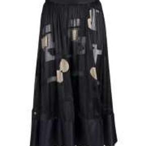 Nederdel fra STINE GOYA style Kirsten viskose/silke kvalitet. Nederdelen har fast talje samt smuk lang længde med bred effekt kant for neden.  Størrelse M.  Længde er omkring 75 cm  Linning er ca 4 cm og måler 38-39 cm fra side til side  livvidde på 76-78 cm.