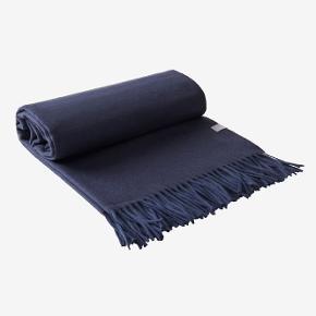 Varm, eksklusiv og luksuriøs plaid i mørkeblå kashmir og uld med frynser i enderne. Kashmir er et af de mest værdifulde naturlige tekstiler i verden.  50% kashmir og 50% uld. Størrelse: 130x170 cm Vaskeanvisning: Kemisk rens.  P R I S   5 5 0,-  (i butikken 1.900,-) Helt ny og i ubrudt emballage.  Fås også i Sort, Blomme og Mørkeblå