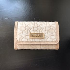 Helt ubrugt pung fra DKNY sælges. Der er 5 rum indeni og 1 udenpå. Der er absolut ingen ridser eller lignende, og den har aldrig været brugt. Pungen er foret med læder og silke indeni.