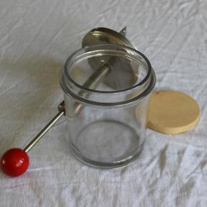 Sjovt gammelt hakkeapparat til løg/krydderurter. I kaftigt glas, metal og med rødmalet træknop.  Der medfølger en træklods, som både muliggør hakning i 2 højder og beskytter knivene, når de ikke er i brug.  Virker fint. Kan bruges i køkkenet og/eller som dekoration.