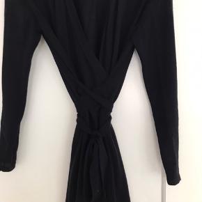 Mørkeblå strikkjole mes bindebånd i taljen. Der er et lille hul bag på kjolen, men det ses minimalt hvis min har bukser eller strømpebukser inden under :-)