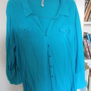 Fin skjorte i viscose med rib i siderne. Den er ikke gennemsigtig, men jeg sender en top med, som jeg købte samtidig med skjorten. Farven er lidt mørkere end skjortens.  Fine detaljer på skjorten med lommer og 3/4-ærmer, der kan knappes kortere.  Bryst: ca. 2 x 50 cm + lidt stræk fra rib-indsatsen Længde ca. 64 cm  JEG BETALER FORSENDELSEN!  Skjorte og top Farve: Turkis