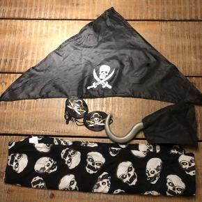 Piratudklædning med:  Tørklæde til hovedet, sort satin Klo, med skjult greb. 2 stk. satin øjenklapper m elastik Bomuldsbandana m dødningehoveder.