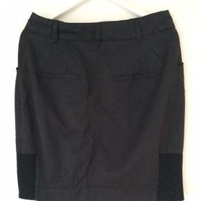 """Varetype: kort sort nederdel Farve: sort Oprindelig købspris: 800 kr.  """"Den lille sorte"""" - nederde!  Fed sort nederdel fra Baba Jaga med mange små detaljer:  2 skrålommmer foran, 2 baglommer, lille elastikstof i nederst på begge sider af nederdelen, 2 indvendige knaplåse til at holde nederdelen på plads.  L: ca. 52 cm. Livvidden er ca. 2x42/43 cm.  Jeg sælger også et Pendulum smykkesæt, der passer godt sammen med denne nederdel. Se billede i Billedgalleri."""