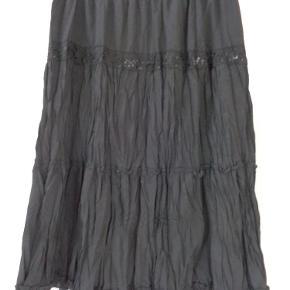Varetype: flot nederdel Størrelse: M/L Farve: Sort  Der er elastik i taljen. Smuk pallietkant øverst Livvidden kan strække sig fra 2 x 42 cm - 2 x 50 cm Længde 65 cm Matriale 100 % bomuld  Nederdelen er med foer