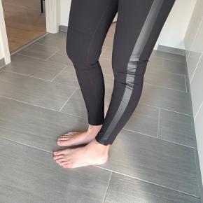 Bukser/leggings med læder detalje ned langs benene.