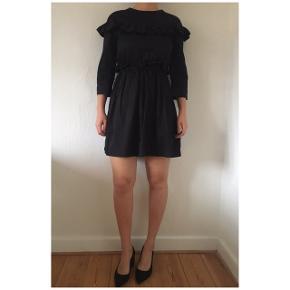 Fineste sorte klassiske kjole fra H&M i str 36 med de skønneste detaljer. Kjolen har lommer i hver side. Lynlås i ryggen. Fine flæser og sidder til i taljen, som giver en god pasform. Ny pris var 499,-. 100% bomuld.