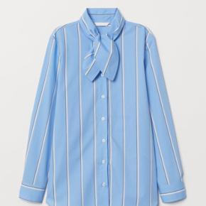 Helt ny skjorte i 100% bomuld. Str. 36  Skjorten har bred krave med bindebånd og knapper foran.
