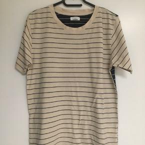 Unik t-shirt fra Wood Wood  str. S sælges. Farve: sand og marineblå. Jeg sender gerne ved betaling med MobilePay og Porto GLS 35 kr. Se også mine andre spændende annoncer :-) 🌸Gratis Porto i efterårsferien ved køb via TS i efterårsferien🍁🍂🤗