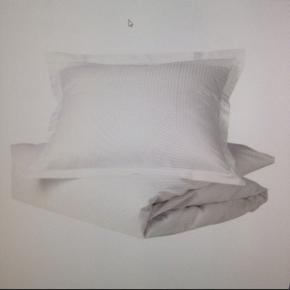 Helt nyt, klassisk og utrolig blødt Georg Jensen Damask sengetøj til baby i eksklusiv 100 % ægyptisk bomulds kvalitet. Er stadig i ubrudt emballage/plastik.   Design: Jette Nevers/Facet. Et smukt og stilrent mønster med enkle geometriske former.   Vaskes v/95 grader. Kan stryges. Må ikke tørretumbles.  Pudebetræk: 40 x 45 cm. Dynebetræk: 70 x 100 cm.  Nypris (Luksus Baby): kr. 489,-