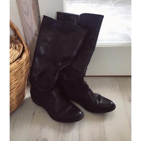 """Sorte støvler fra tamaris. Går til under knæet. Slid i form af """"rynke"""" på snuden, der retter sig en del ud når man har dem på. Fine under bunden. Hæl på et par cm.  Kan afhentes i Århus eller Vejle, eller sendes med DAO:)"""