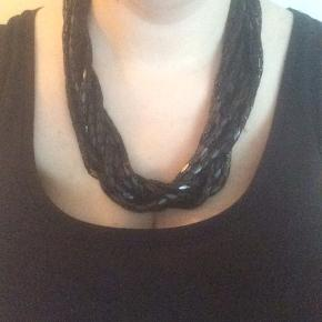 Sort halskæde med små metalvedhæng. Kan justeres i de små og store ringe