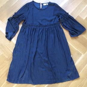 Smuk kjole med trekvarte ærmer. 100% polyester med et fint blankt skær. Knap i nakken. Længde 80 cm. Brystvidde 40*2 cm