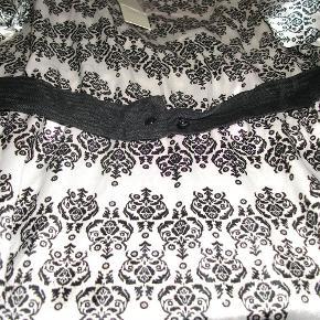 Super lækker kjole i 100 % polyester.  V-hals og bælte foran og bagpå  Kjole Farve: Hvid/sort Oprindelig købspris: 399 kr.