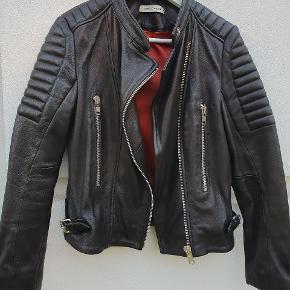 Rå Sofie Schnoor bikerjakke i lammeskind, med rødt inderfor. Inderforet har lidt misfarvninger, men jakken fejler ellers intet. Koster omkring 2500,- fra ny.  Brugt ca. 2 gange. (Billedet giver jakken en misvisende nuance. Den er helt sort og blød.)