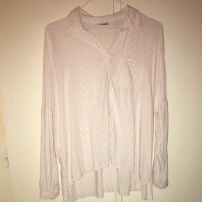 Fin skjorte, som er længere bagpå end foran. Er i pæn stand. Kan sendes på købers regning eller hentes i Helsingør, Holte eller på Frederiksberg.