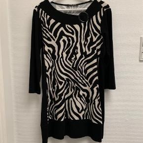 Varetype: Kort Farve: Sort Prisen angivet er inklusiv forsendelse.  Zebra print, Betty Barclay kjole/tunika med 3/3 lange ærmer og bådformet halsudskæring. 92% viscose og 8% elastan Længde fra skulderen er ca. 83 cm, brystvidden er ca. 98 cm