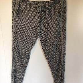 Lækre lette Rosemunde bukser med elastik i livet. Grå/sort med blonde langs benet   Har været brugt nogle gange med i rigtig flot stand