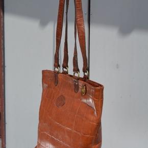 Smuk cognacfarvet mulberrytaske i det ikoniske croc-læder. Meget velholdt og velegnet til shopping ☀️ Den har en lille blækplet i bunden (udvendigt) - den slags går som regel væk ved brug, når der er tale om læder. Man ser dog ikke pletten når tasken er på :-) Giv endelig et bud 😊