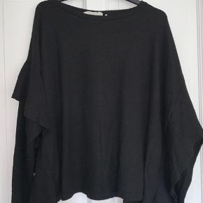 Sort fleece trøje med flagre ærmer.