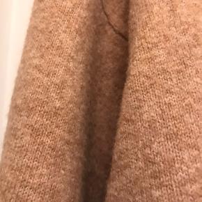 Dejlig oversize strik i blød kvalitet. Med krave der både kan bukkes om og falde løst. Det er en small men i oversize størrelse. Passer også en medium.  I fin camel farve.  Brugt få gange.  Køber betaler Porto.  Den består af polyester, uld, akryl og elastan. God blød kvalitet. Længde ca. 80 cm. Så pæn til tætte jeans.