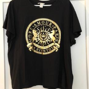 T-shirt med guldprint.  Brugt 1 gang. Der er en lille 'skygge' bag på ved skulderen, se sidste billede, derfor sælges den billigt.  Bytter ikke.  OBS: Jeg sender kun ved en evt. handel.