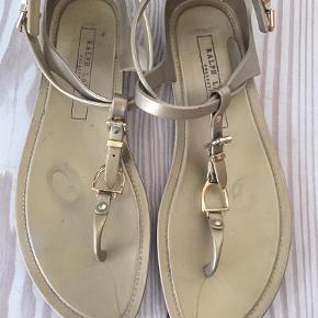 Varetype: Guldsandaler Sandaler Størrelse: 9 Farve: Guld Oprindelig købspris: 1000 kr.  Guldsandaler - Superfine plast sandaler i guld fra Ralph Lauren. Fine gulddetaljer. Behagelige at have på. Nypris kr 1000. Vil gerne tages på en eksotisk strand 😎☀️