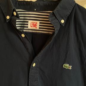 Lacoste mørkeblå skjorte i 100% bomuld. Str. 40. God stand.